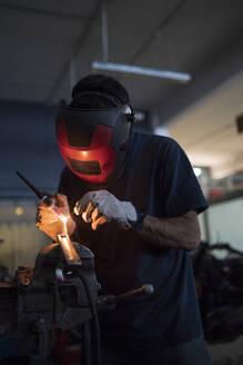 Mechanic in a repair garage welding - MTBF00177
