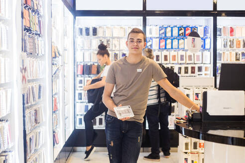 Portrait of confident young salesman holding phone cover while standing by checkout with customers in background - MASF14338