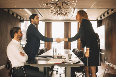 Male and female lawyers shaking hands in board room at office - MASF14497