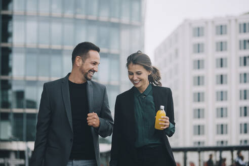 Smiling businesswoman and businessman talking while walking in city - MASF14638