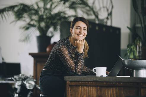 Portrait of smiling businesswoman with hand on chin sitting at kitchen island in creative office - MASF14680