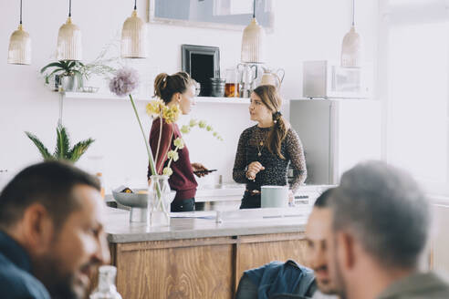 Creative female entrepreneurs discussing at kitchen island while colleagues in foreground at office - MASF14692