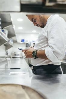Chef using smartphone in the kitchen - MTBF00198