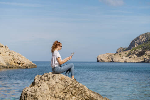 Redheaded woman sitting on rock and reading magazine - AFVF04194