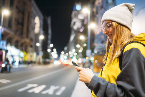 Smiling young woman in the city using her smartphone at night - JCMF00289