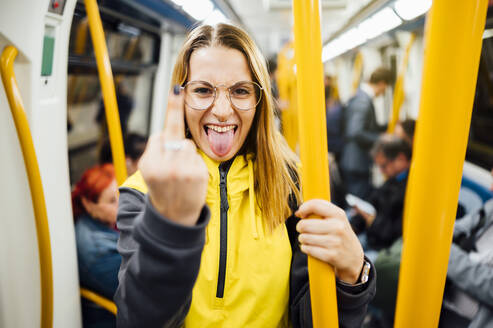 Young woman standing in underground train giving the finger - JCMF00292
