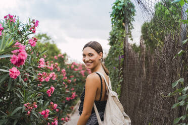 Portrait of smiling young woman with backpack strolling in a park - AFVF04204