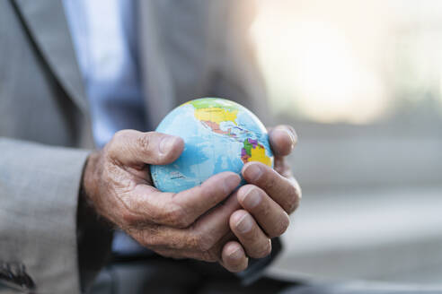 Close-up of hands of businessman holding globe - DIGF08881