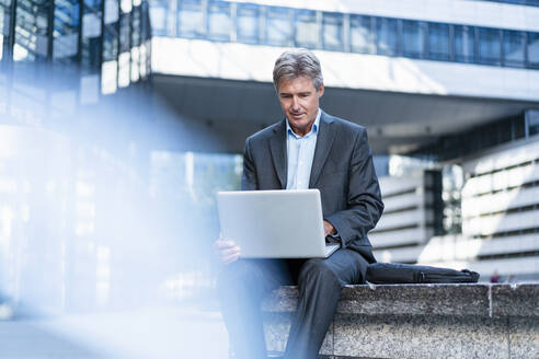 Mature businessman using laptop in the city - DIGF08890