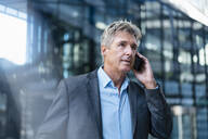 Mature businessman on the phone in the city - DIGF08896