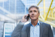 Mature businessman on the phone in the city - DIGF08902