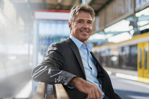 Portrait of smiling mature businessman waiting at station platform - DIGF08914
