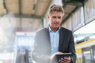 Mature businessman using tablet at station platform - DIGF08917