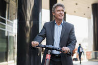 Mature businessman with e-scooter in the city - DIGF08920