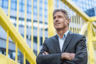Portrait of confident mature businessman on a bridge - DIGF08923