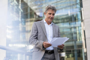 Mature businessman reviewing documents in the city - DIGF08935