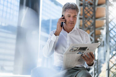 Mature businessman with newspaper on the phone in the city - DIGF08956
