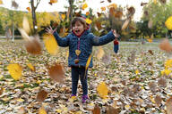Little girl playing with autumn leaves outdoors - GEMF03298