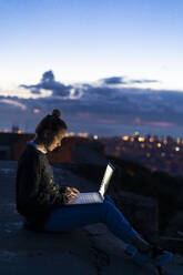 Young woman using laptop at dawn above the city, Barcelona, Spain - GIOF07690