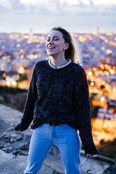 Happy young woman at dawn above the city, Barcelona, Spain - GIOF07693