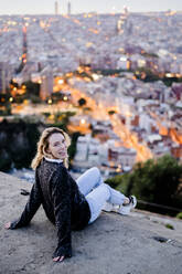 Portrait of happy young woman at dawn above the city, Barcelona, Spain - GIOF07696