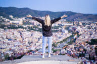Rear view of carefree young woman standing above the city at sunrise, Barcelona, Spain - GIOF07699