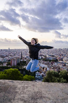 Carefree young woman jumping above the city at sunrise, Barcelona, Spain - GIOF07702
