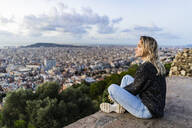 Young woman sitting above the city at sunrise, Barcelona, Spain - GIOF07705