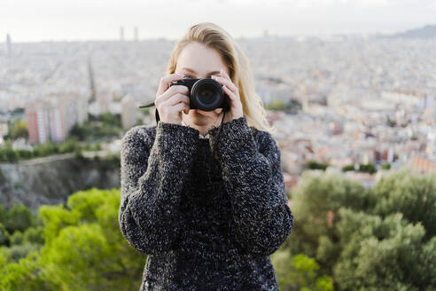 Young woman taking pictures above the city at sunrise, Barcelona, Spain - GIOF07708