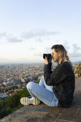 Young woman taking pictures above the city at sunrise, Barcelona, Spain - GIOF07711