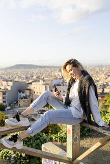 Young woman sitting on railing above the city using cell phone, Barcelona, Spain - GIOF07717