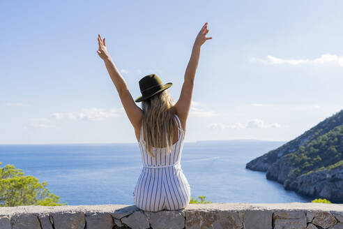 Young woman sitting on a wall with raised arms and looking at distance, viewpoint in Ibiza - AFVF04224