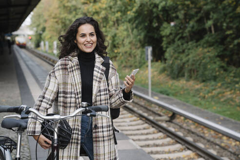 Smiling woman with bicycle and cell phone on an underground station platform, Berlin, Germany - AHSF01196