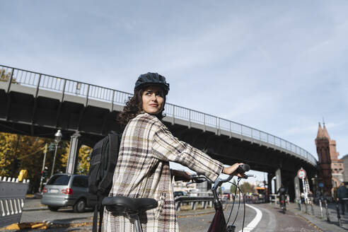Woman with a bicycle in the city, Berlin, Germany - AHSF01223