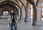 Happy woman riding bicycle in the city, Berlin, Germany - AHSF01226