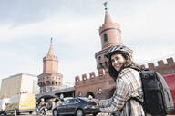Smiling woman with a bicycle in the city at Oberbaum Bridge, Berlin, Germany - AHSF01229