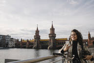 Smiling woman with bicycle and smartphone in the city at Oberbaum Bridge, Berlin, Germany - AHSF01232