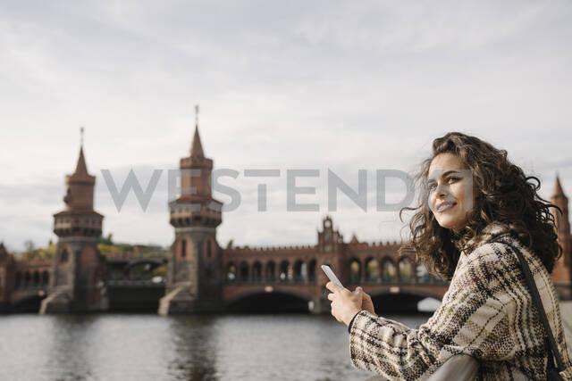 Smiling woman with smartphone in the city at Oberbaum Bridge, Berlin, Germany - AHSF01235 - Hernandez and Sorokina/Westend61