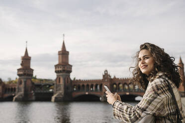 Smiling woman with smartphone in the city at Oberbaum Bridge, Berlin, Germany - AHSF01235