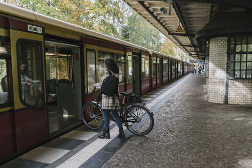 Woman with bicycle entering an underground train, Berlin, Germany - AHSF01241