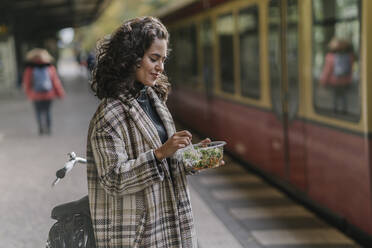 Woman having lunch on an underground station platform, Berlin, Germany - AHSF01244
