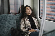Young woman with closed eyes relaxing on a subway - AHSF01253