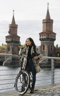 Smiling woman with bicycle on the phone in the city at Oberbaum Bridge, Berlin, Germany - AHSF01256