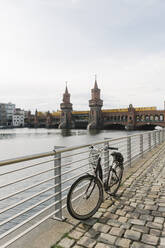 Parked bicycle with Oberbaum Bridge in background, Berlin, Germany - AHSF01259