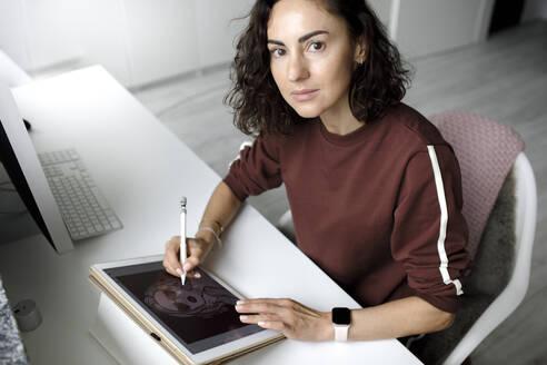 Female web designer using tablet at home, looking at camera - KMKF01143