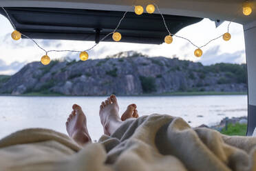 Feet of teenage couple, lying in a camper at the sea - LBF02790