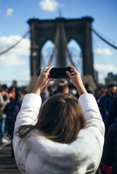 Woman taking a picture of Brooklyn Bridge, New York, United States - OCMF00895