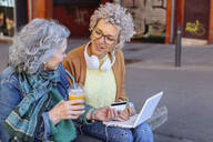 Senior mother with her adult daughter shopping online together in the city - RTBF01385