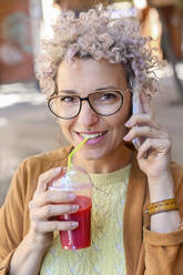 Portrait of a woman using smartphone and drinking a juice outdoors - RTBF01388