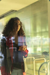 Portrait of pensive young woman with cell phone standing behind glass pane looking at distance - ERRF02034